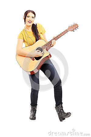 Young female musician playing an acoustic guitar