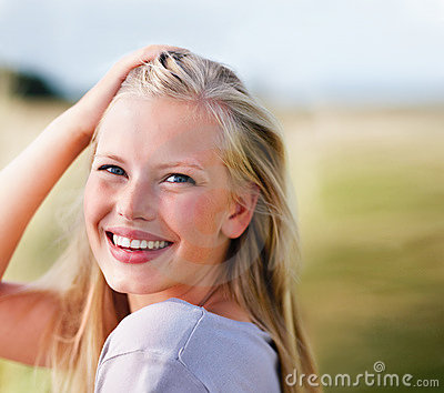 Young female playing with hair, smiling outdoors
