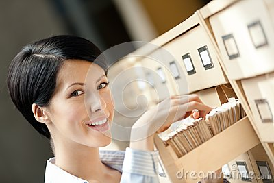 Young female searches something in card catalog