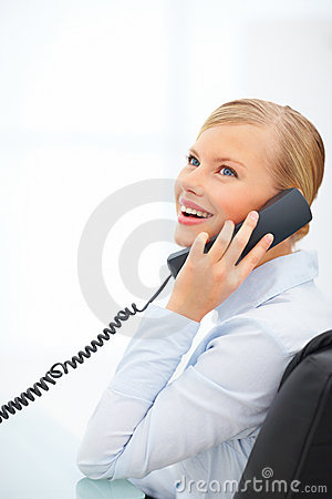 Young female speaking on telephone over white back