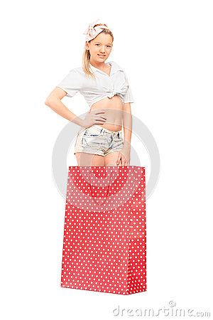 A young female standing into a red spotted shopping bag
