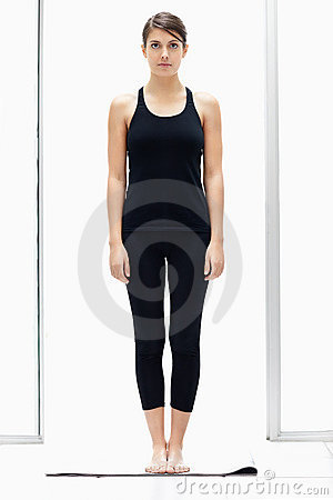 Young Female Standing Straight On A Yoga Mat Stock Photo