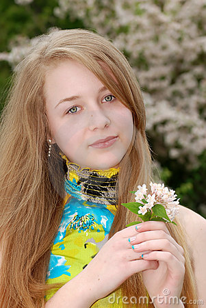 Young female teenager holding flowers in a garden