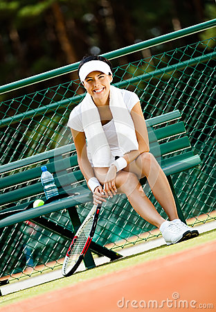 Young female tennis player rests at the bench