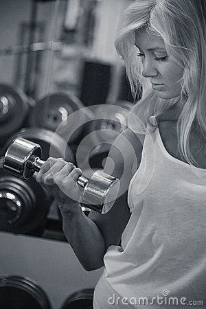 Young female training biceps in gym