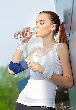 Young fit activity woman drinking water