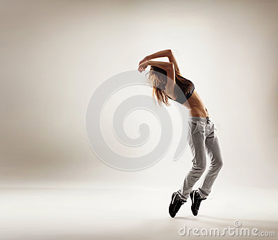A young and fit woman dancing in sporty clothes