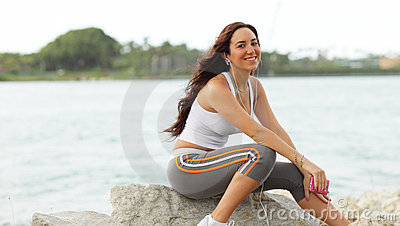 Young fitness model sitting on the rocks