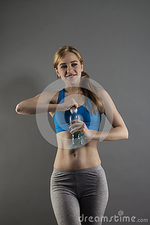 Young fitness woman opening a bottle with water
