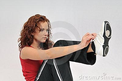 Young fitness woman ties lace on her shoe