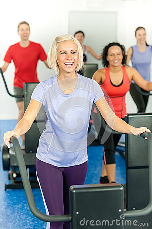 Young fitness woman at treadmill running class