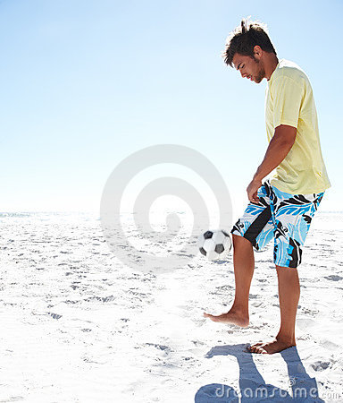 Young football player at the beach