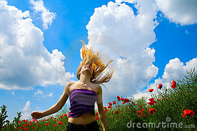Young free happy woman in poppy field