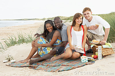 Young Friends Enjoying Picnic On Beach