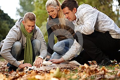 Young friends having autumn fun in park