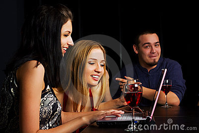 Young friends with laptop in a bar