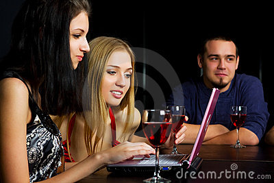 Young friends with laptop in a bar.