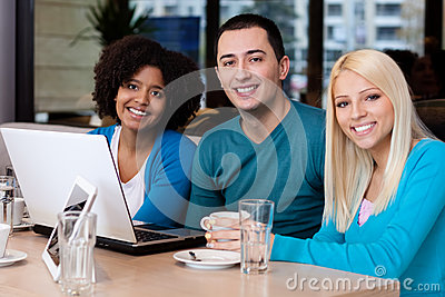 Young friends with laptop in cafe