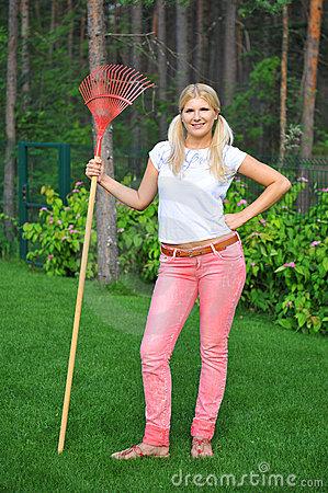 Young gardening woman with rakes