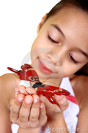 A young girl admiring a beautiful red butterfly