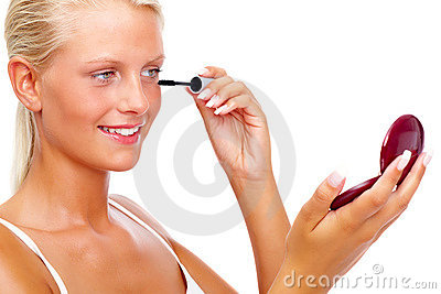 Young girl applying mascara against white