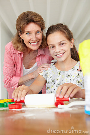 Young girl baking with grandmother at home