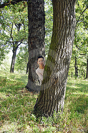 Young girl behind the tree on warm summer day