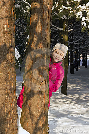 Young girl behind a tree in wood, hiding
