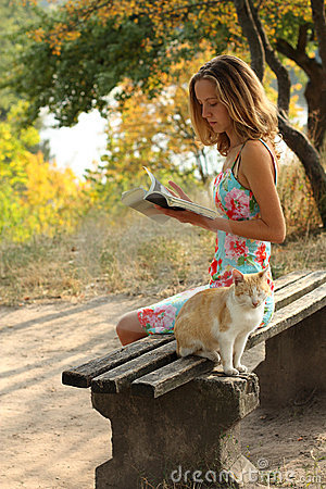 Young girl with a book and a cat