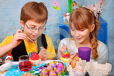 Young girl and boy painting easter eggs