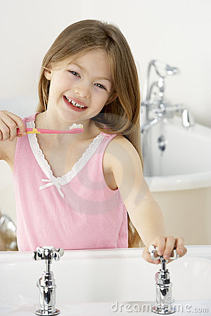 Young Girl Brushing Teeth at Sink