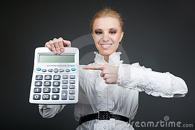 Young girl with calculator on grey