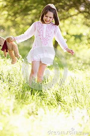 Young Girl Carrying Teddy Bear In Field