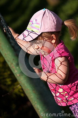 Young girl climbing on fence