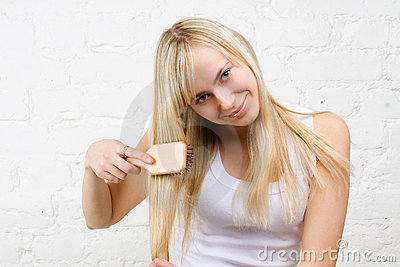 Young girl combing blonde hair