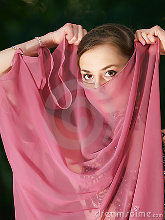 Young girl covers face like arabic woman