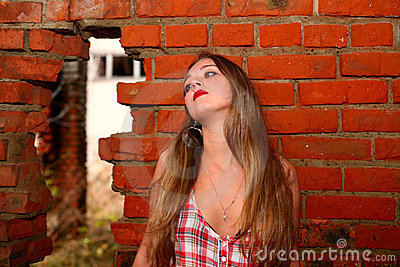 Young girl cries about a brick wall