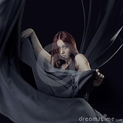 Young girl dancing with long grey cloth