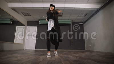Young girl dancing modern dance in black clothes. Dancer makes a quick and active movements of arms and legs during her. Dance. Rehearsal in the dance studio stock footage