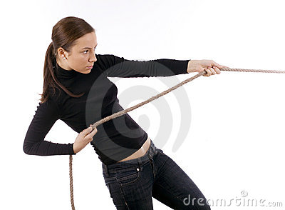 Young girl in dark clothes pulling grey rope