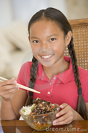 Young girl in dining room eating chinese food