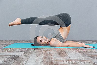 Young girl doing yoga exercise Halasana (Plow Pose) Stock Photo