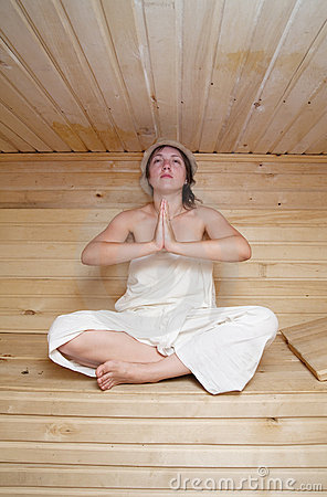 Young girl doing yoga  in a sauna