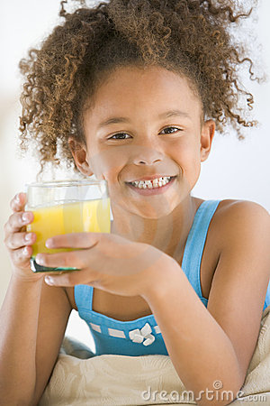 Young girl drinking orange juice in living room