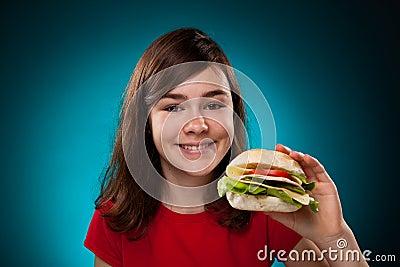 Young girl eating big sandwich