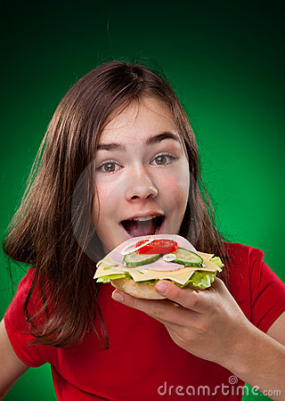 Young girl eating big sandwich