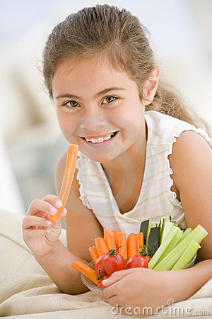 Young girl eating bowl of vegetables