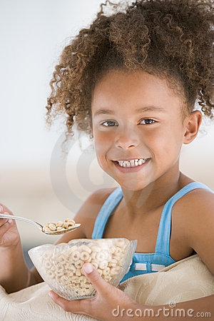 Young girl eating cereal in living room