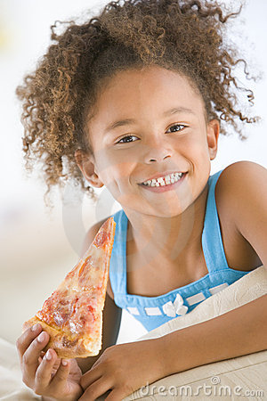 Young girl eating pizza slice in living room