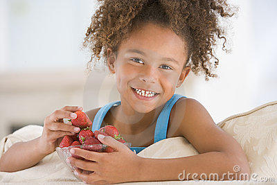 Young girl eating strawberries in living room